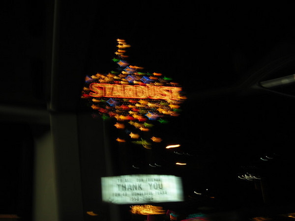 The doomed Stardust<br /> <br /> It's not a good photo (taken from a moving bus...) but I wanted to get a shot of the flashy Stardust sign. This classic casino is now closed and will shortly be demolished for another bigger, flashier model.