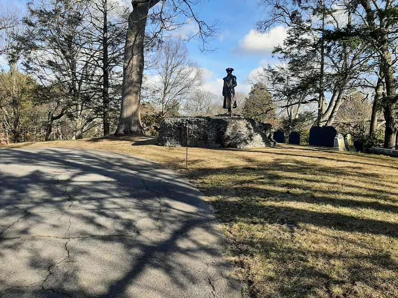The Warren family plot is at the highest point along  Mount Warren Avenue,  on the outside of the sharp curve. A statue of Warren, which is a smaller copy of the statue at Roxbury Latin School, was placed atop the rock out-cropping by the Masons in 2016. This is the view as you drive up Mount Warren Avenue.