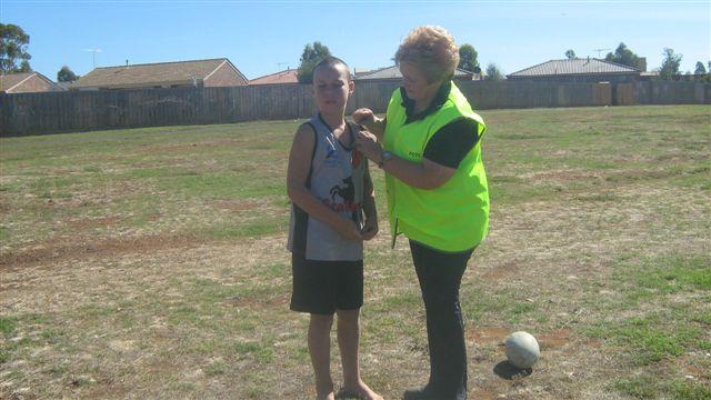 Lyn presenting Kane with his volunteer badge