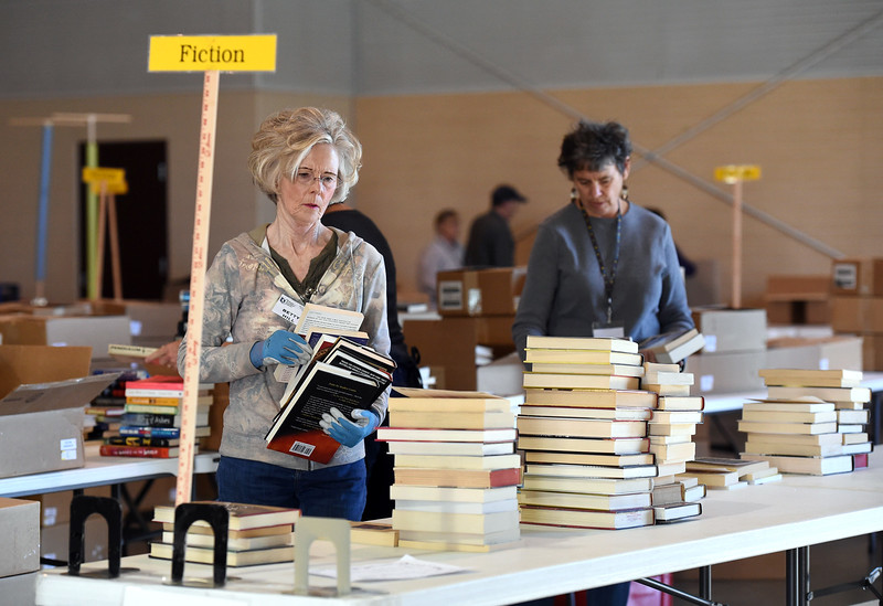 Volunteer Betty Hill places books on a table Wednesday, Oct. 25, 2017, in preparation of the Friends of the Loveland Public Library Used Book Sale this weekend at The Ranch in Loveland.   (Photo by Jenny Sparks/Loveland Reporter-Herald)