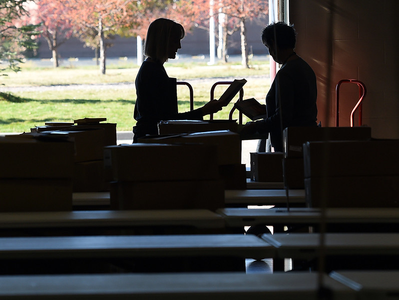 Ann Marie Rozum, left, and Peggy Kindschy, volunteers with the Friends of the Loveland Public Library, are silhouetted as they unpack boxes of books Wednesday, Oct. 25, 2017, in preparation of their used book sale this weekend at The Ranch in Loveland.   (Photo by Jenny Sparks/Loveland Reporter-Herald)