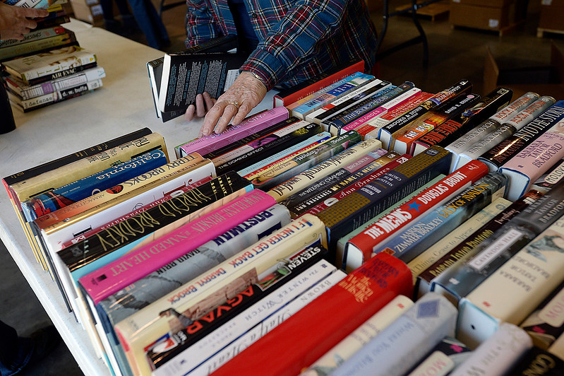 Volunteer Sue Drage places books on a table Wednesday, Oct. 25, 2017, in preparation of the Friends of the Loveland Public Library Used Book Sale this weekend at The Ranch in Loveland.   (Photo by Jenny Sparks/Loveland Reporter-Herald)