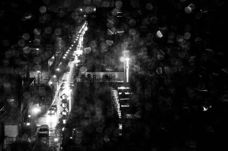 Pedestrian crosses the street on a rainy Mexico City night.