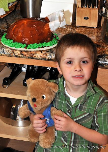 A bear and a boy protect the ice cream cake turkey.