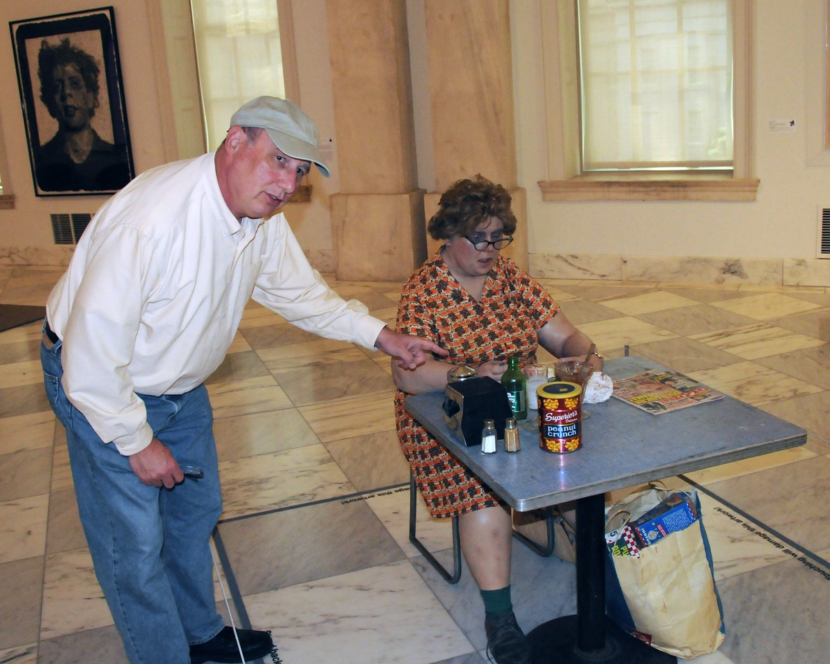 Joe helping an elderly art patron