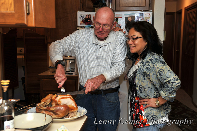 Quint carves the turkey while Claire supervises his work.