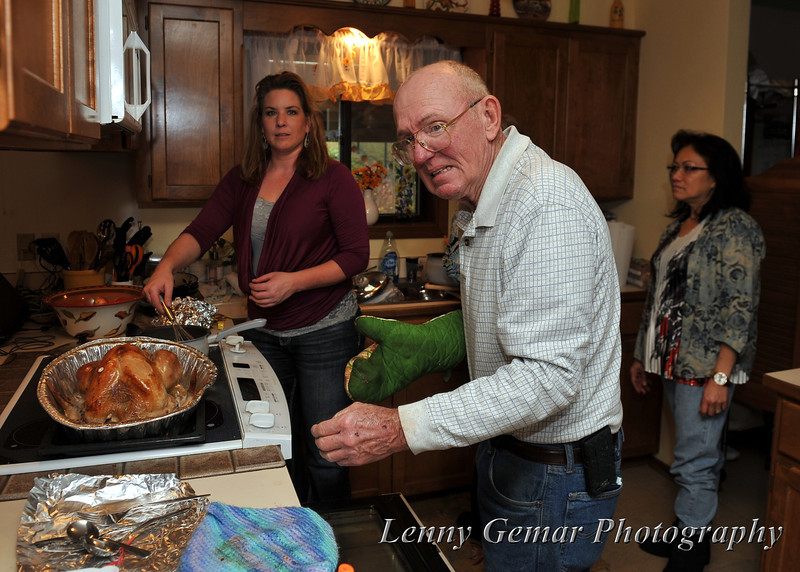 As Laurie and Claire look-on, Quint dons an oven mitt in preparation for moving the turkey.