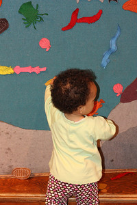 Esther plays with the felt board.