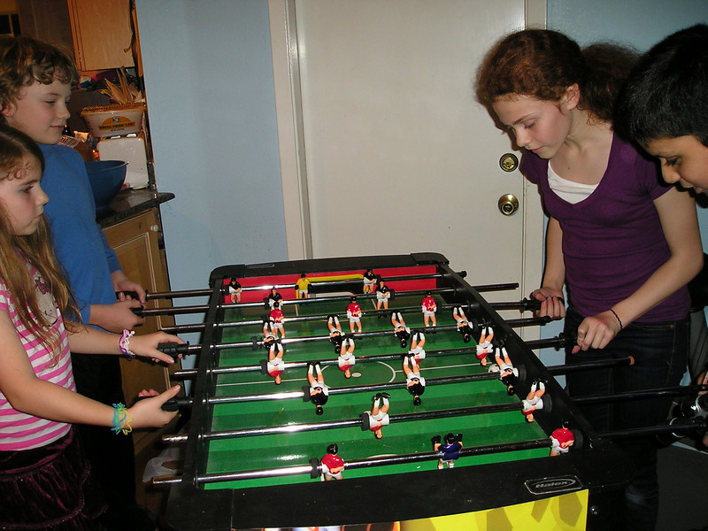 Alex and friends play foosball.