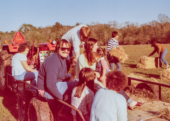 Steve going for a hayride at Marvin Farmer's place in the country.  Jack is over his shoulder, with Heather, about 1 1/2 or 2 years old, so this much be about 1979 or 1980.  Our good friends John Bolling, in the striped shirt, and Tom Marler are in the field getting hay.