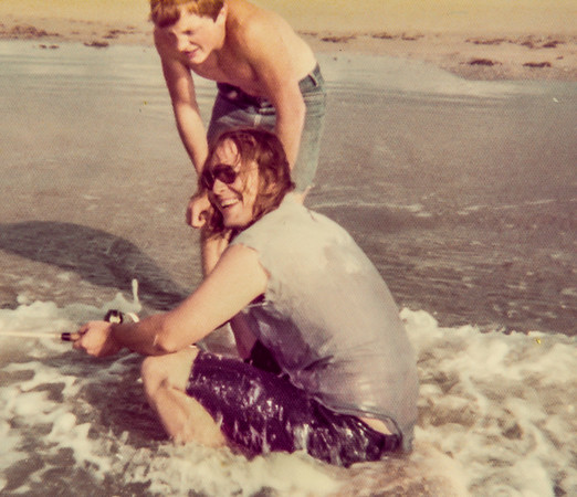Steve fishing in the waves while Charles Montgomery watches. 1976