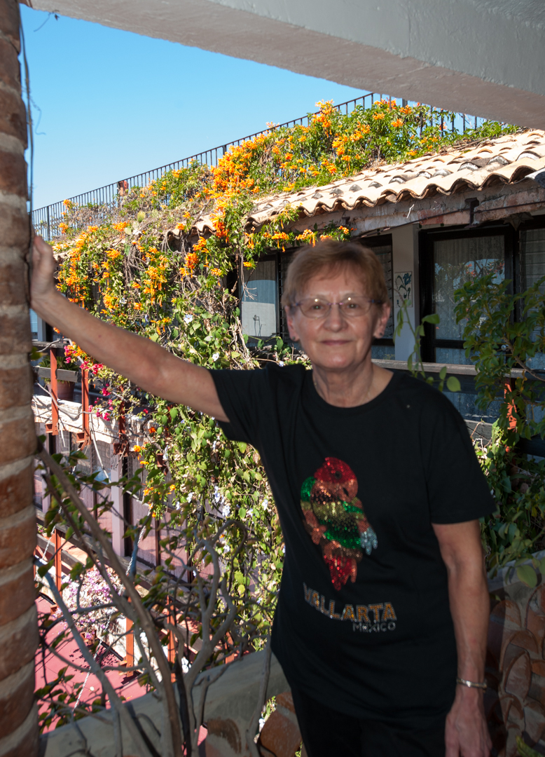 Eileen, with her new T-Shirt, on our 3rd floor balcony at the 4 Winds Hotel.  That's her room over back of her, little left.