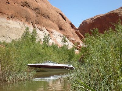 Boat in the middle of nowhere, below redrock wall bleached out by Lake Powell during higher water.