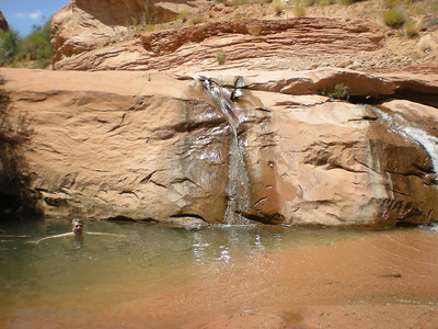 Lower Willow Gulch waterfall, with Tom in plunge pool.  This whole feature was previously submerged beneath the waters of Lake Powell, but is now exposed due to the long-term drought conditions lowering the level of the lake.
