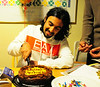 """The first time Aziz has ever cut a cake.  Mohammed is on the right, saying """"go slow."""""""