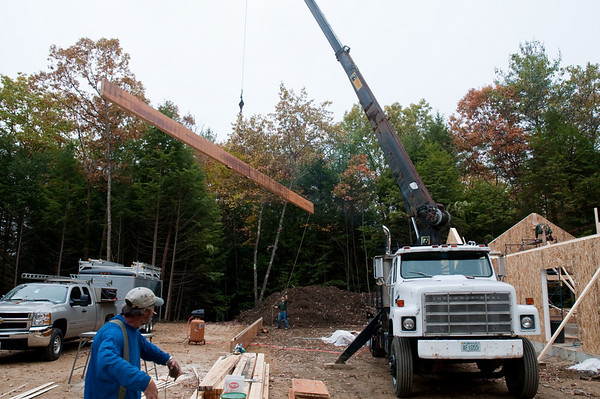The crane truck begins lifting the worship room ridge beam, guided by the man at the far end who controls the swing.