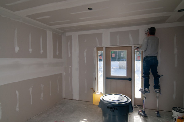 """The final coat of """"mud"""" goes on the drywall seams"""