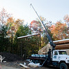 The crane truck swings the SIPs roof panel up.