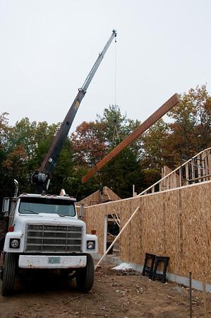 The worship room ridge beam swings into place.
