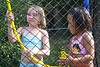 Faith and Abby playing on the trampoline with the water hose