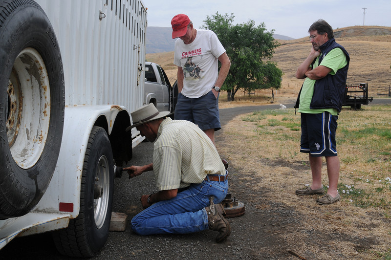 A cowboy in the very small town of White Bird, Idaho, replaces the hub on the trailer. All the lug bolts had sheered off somewhere on the drive south from Hayden, Idaho.
