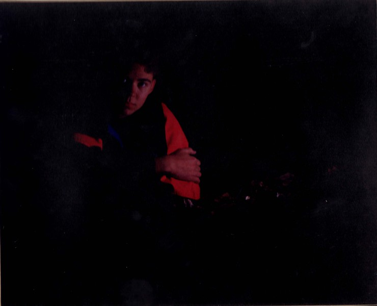 Self portrait taken my senior year of High School.  I shot this in a small cave at Whips Ledges in Hinckly Ohio lit only with a single off camera flash.  There is glare in the scan which is due to my less than optimal scanner setup - not the print.