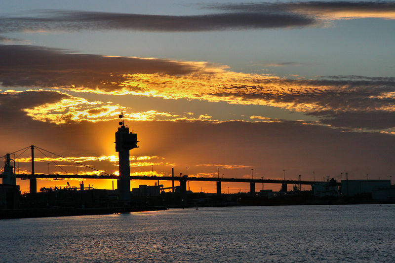 The sun sets behind the control tower for the Port of Melbourne and the Westgate Bridge.