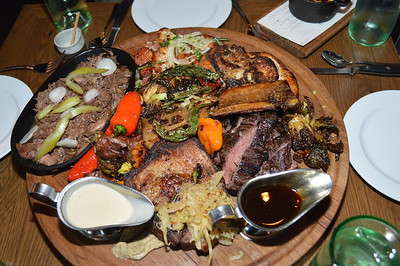 Mixed grill for four; clockwise, chicken, steak, pork, braised lamb, peppers, sweet potatoes, sauerkraut, brussel sprouts