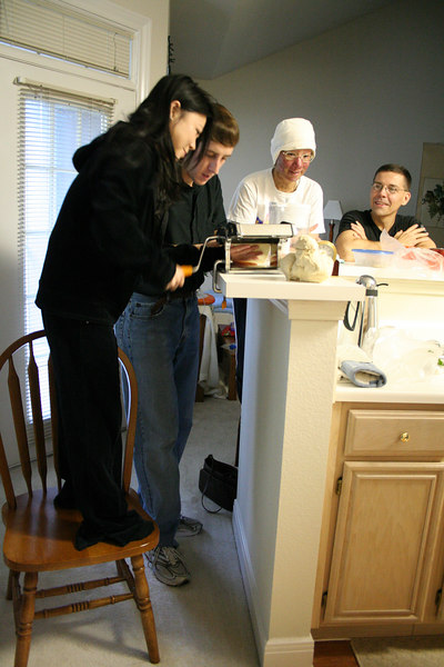 Thuy, Adam, Thi, and Mark diligently practice the art of making dumpling skins with Eddy's pasta maker.