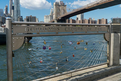 Locks — a new tradition under and on the Brooklyn Bridge. We're standing at the edge of the East River.