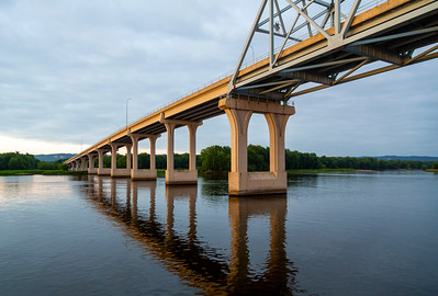 Sailing under a Mississippi bridge at twilight