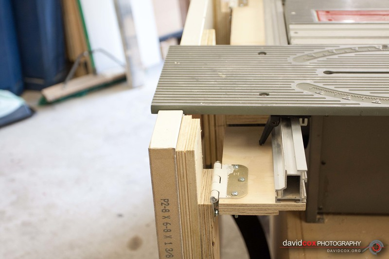 Closeup detail of rail mounting of Flip-up folding outfeed table for my Ryobi BT3000 tablesaw made from an recycled hollow core door with sliding miter table extended and outfeed table in down position