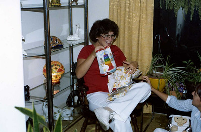 Hillary unwrapping gifts from baby shower for Andrew. Andrew was born December of 1980. This turned out to be a very favorite toy.