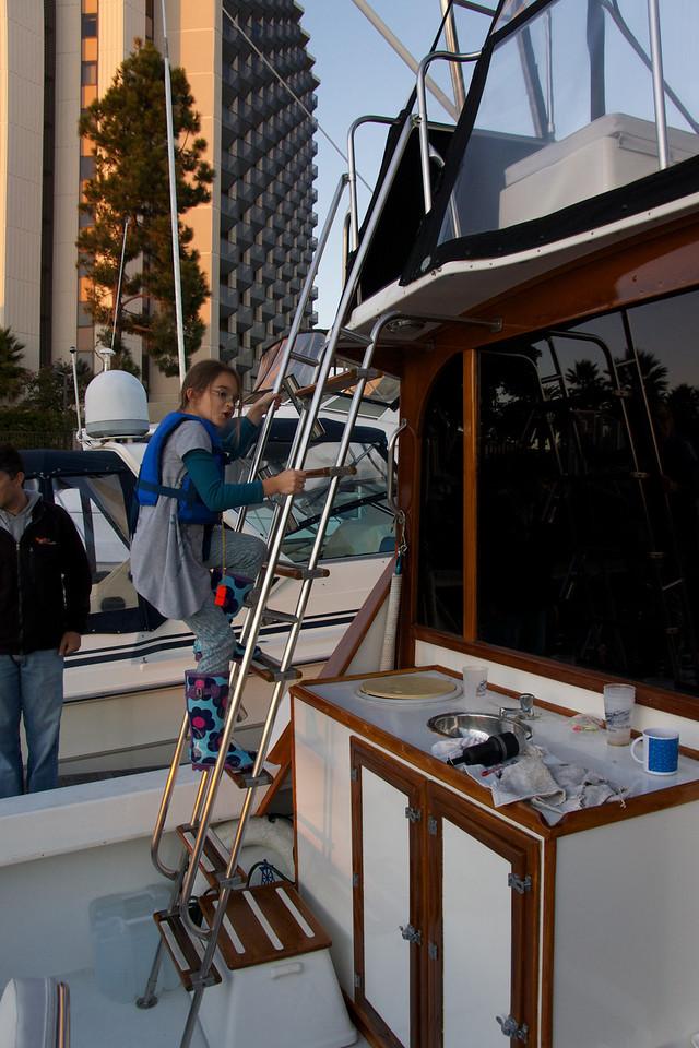 Katerina climbs ladder to pilot house