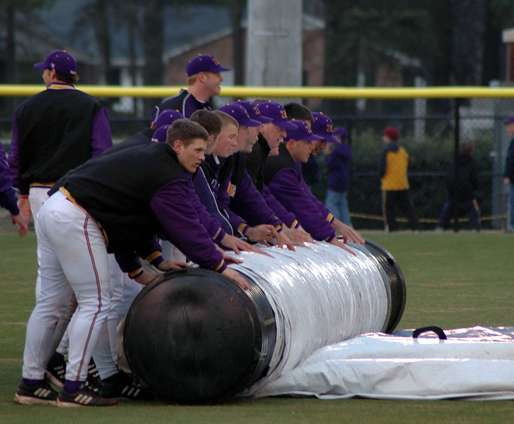The ECU team uncovering the field after a rain delay halted play in the afternoon game.