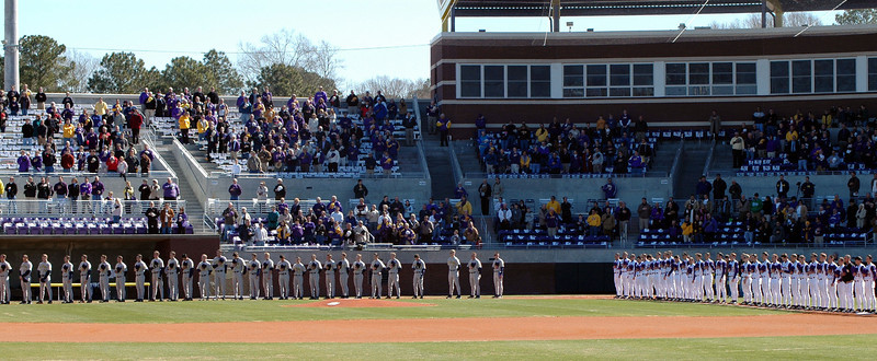 The ECU and Michigan baseball teams during the national anthem of the opening game of the Keith-LeClair Invitational.