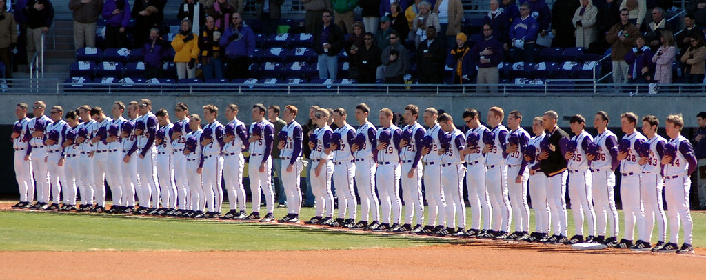 The ECU Baseball team standing on the 3rd baseline during the National Anthem.