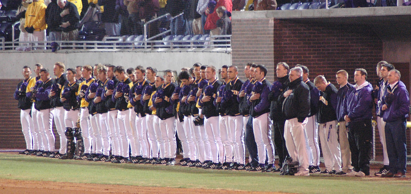 The ECU Baseball team lined up on the 3rd base line for the national anthem.