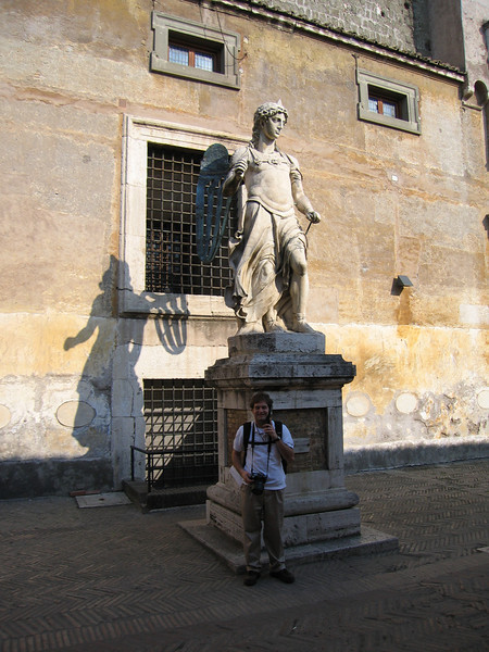 Jon listening to his audio guide in front of a statue in Castel Sant'Angelo.