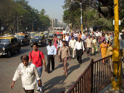 Street scene of taxis and people walking to work in Mumbai during rush