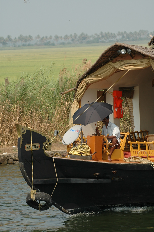 Driver at the helm of his house boat equipped with a satellite dish