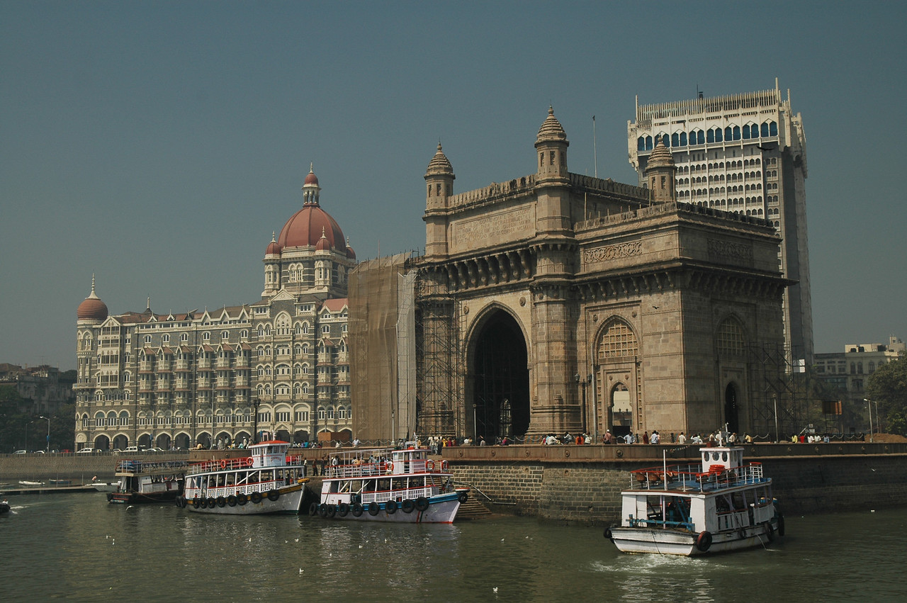 Tour boats docked in front of the Taj Mahal Hotel and India Gate