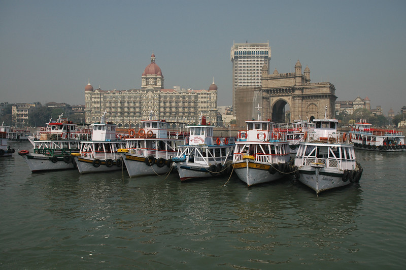 Tour boats anchored in the harbor in front of the Taj Mahal Hotel and India Gate