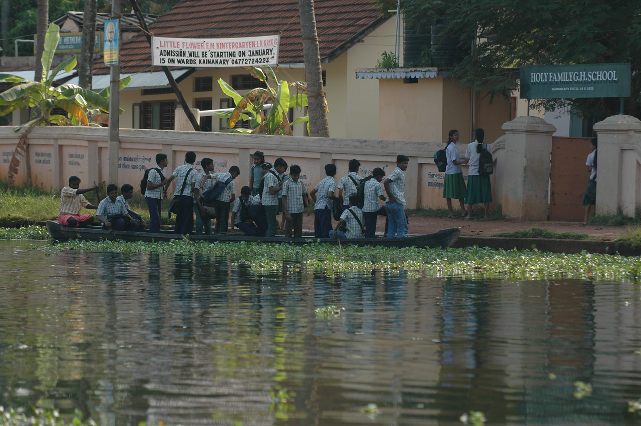 School children getting off a boat on their way home from school in the backwaters of Kerala