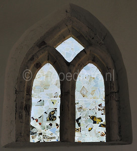 Pprspronkelijk gotisch venster, gevuld met fragmenten laat-middeleeuws vensterglas