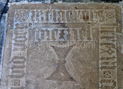 Detail van de bentheimer zandstenen zerk met gotisch randschrift en zandloper