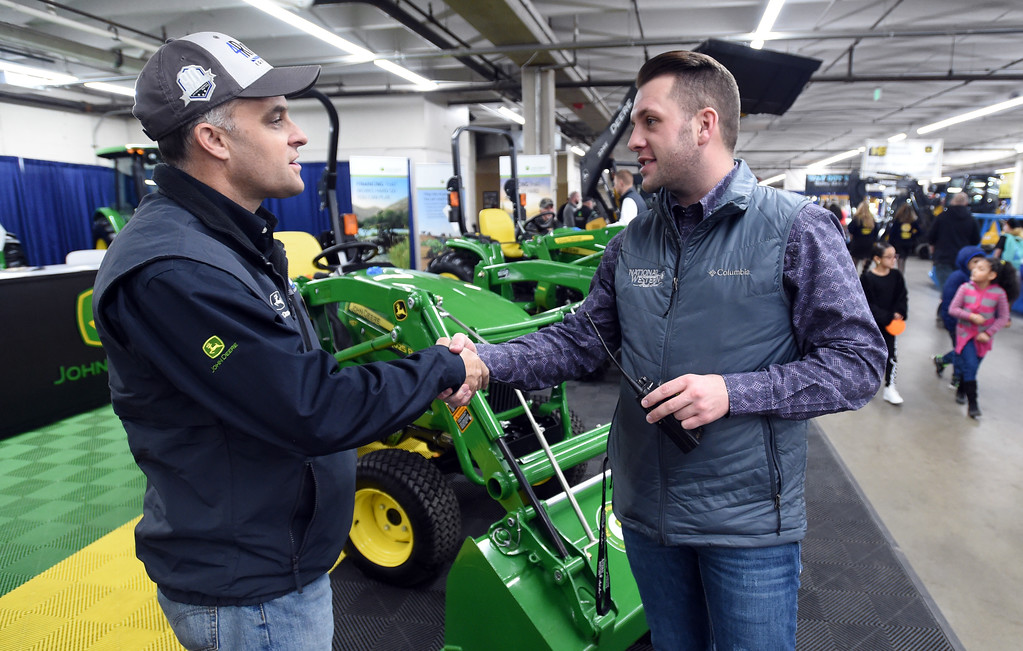 . Clay Johnson, right, Sponsorship Account Manager, talks to Ryan Winberg, a John Deere salesman, in the vendor building on Thursday. Three people who grew up  in Boulder County competing as 4-H Club members at both the Boulder County Fair and the National Western Stock Show, are now part of the team running the event in Denver.   For more photos, go to www.timescall.com. Cliff Grassmick  Staff Photographer  January 12, 2017