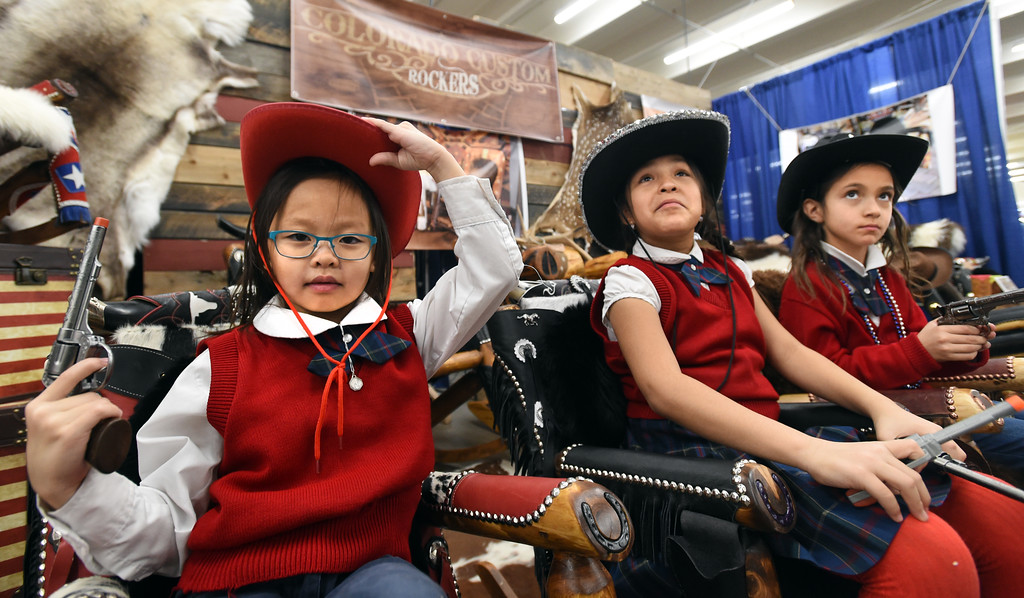 . Nhu Nguyen, left,  Alli Vigil, and Amanda Aleman, try out the rockers at the Colorado Custom Rockers booth. Three people who grew up  in Boulder County competing as 4-H Club members at both the Boulder County Fair and the National Western Stock Show, are now part of the team running the event in Denver.   For more photos, go to www.timescall.com. Cliff Grassmick  Staff Photographer  January 12, 2017