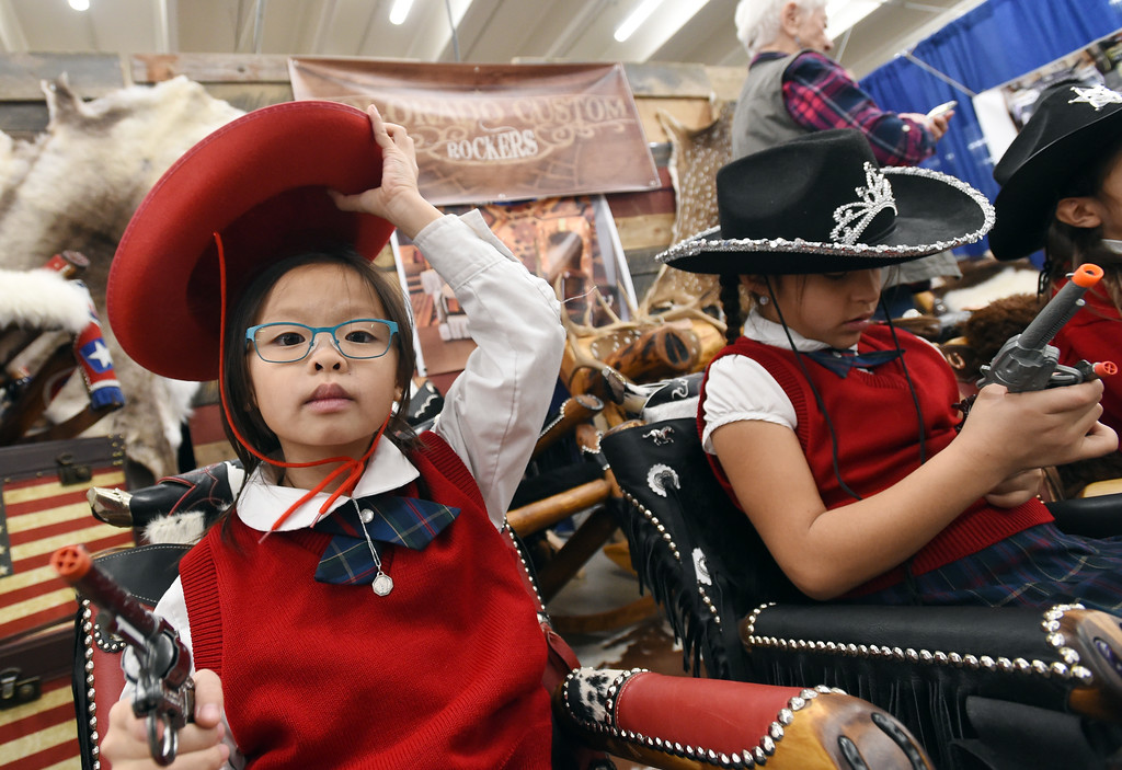 . Nhu Nguyen, left, and Alli Vigil, try out the rockers at the Colorado Custom Rockers booth. Three people who grew up  in Boulder County competing as 4-H Club members at both the Boulder County Fair and the National Western Stock Show, are now part of the team running the event in Denver.   For more photos, go to www.timescall.com. Cliff Grassmick  Staff Photographer  January 12, 2017