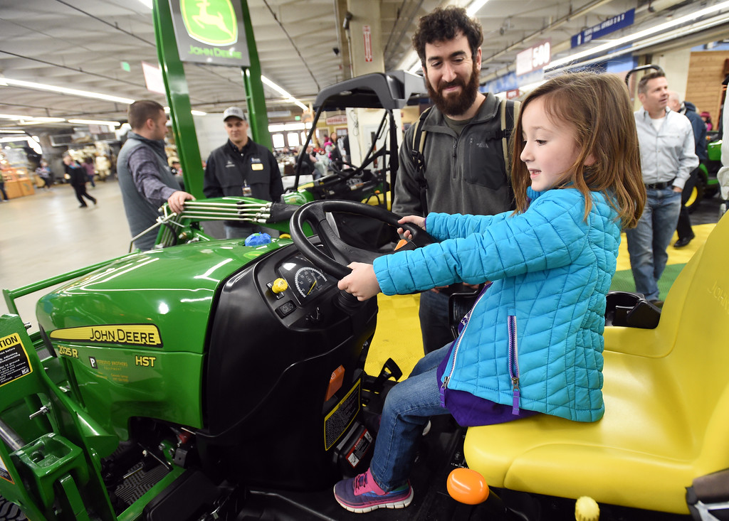 . Ayala Epstein, tries out a John Deere tractor, with her dad, David, in the vender building on Thursday. Three people who grew up  in Boulder County competing as 4-H Club members at both the Boulder County Fair and the National Western Stock Show, are now part of the team running the event in Denver.   For more photos, go to www.timescall.com. Cliff Grassmick  Staff Photographer  January 12, 2017